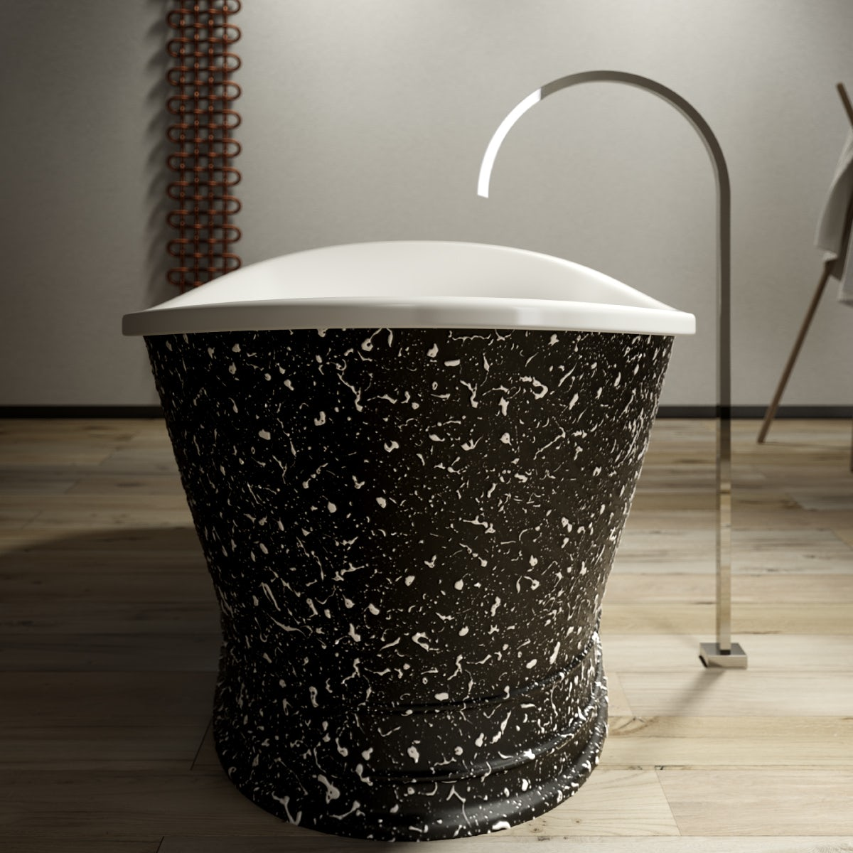 A head-on view of the of the black and white speckled Balthus freestanding bath; with a contemporary Avanzi tall freestanding tap