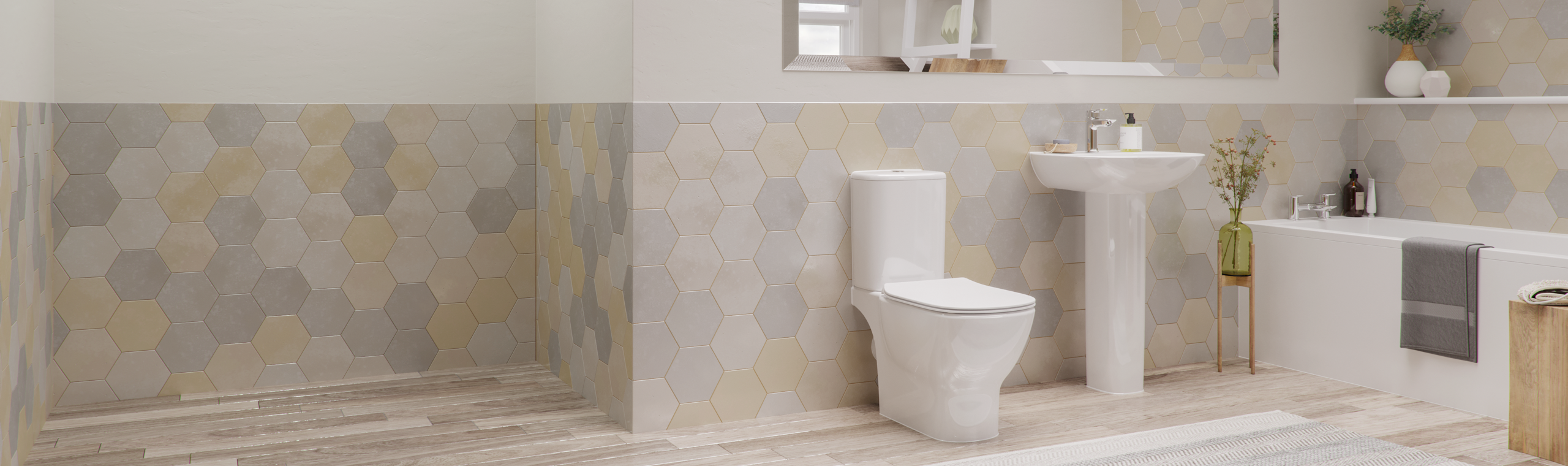 An contemporary Ideal Standard bathroom suite featuring a toilet, sink and bath
