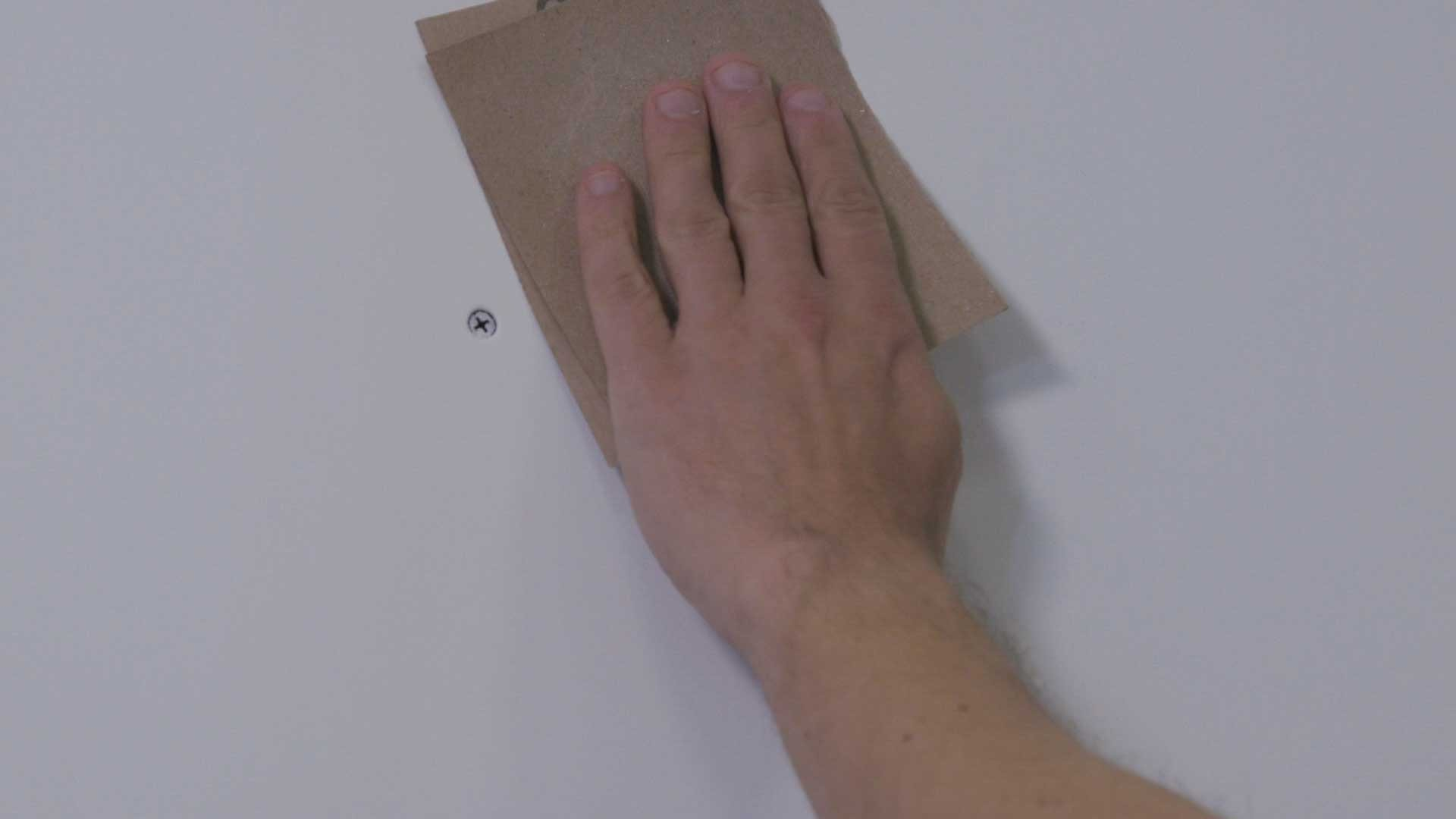 Giving the painted wall a light sanding