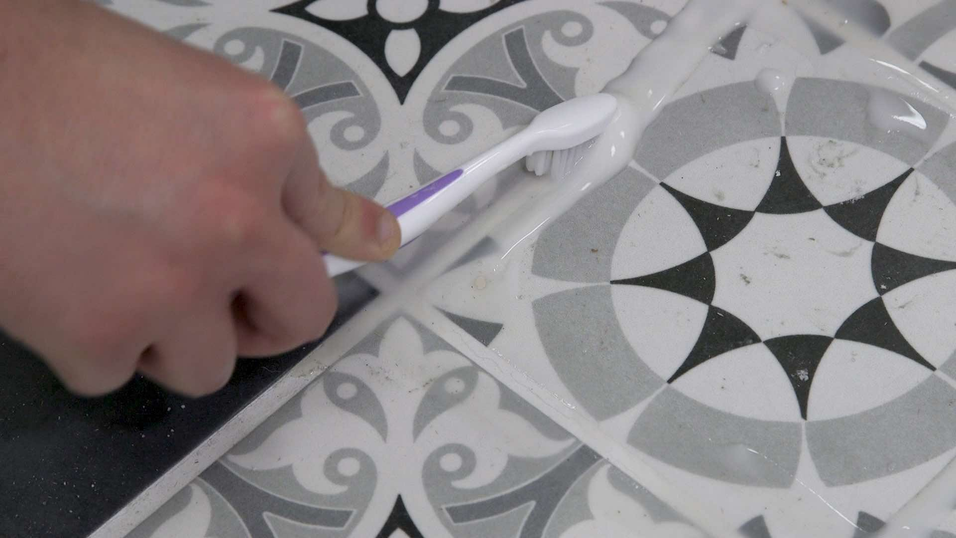 Scrubbing grout with a toothbrush