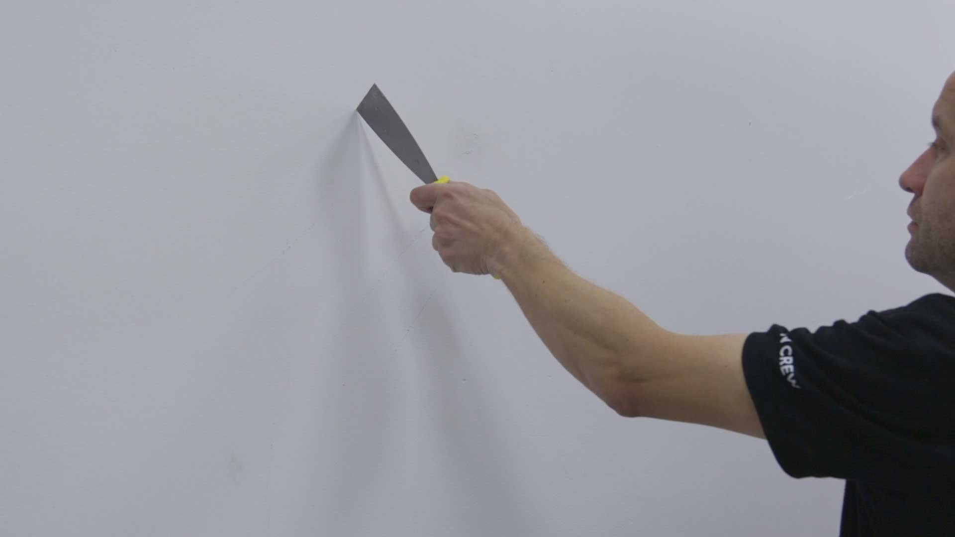 Scoring a fully painted or freshly plastered wall with a scraper