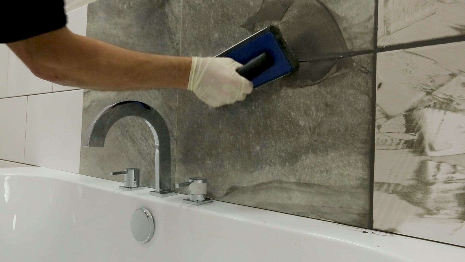Apply grout to tiles using a grout float
