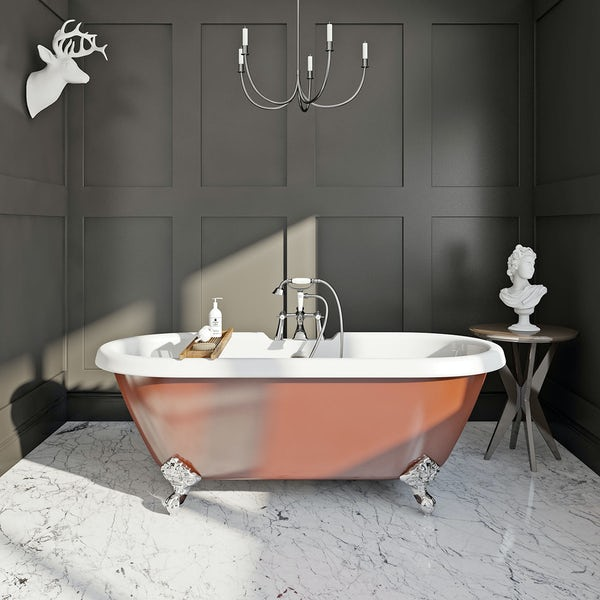 Russet coloured roll top bath in a dark room and marbled floor